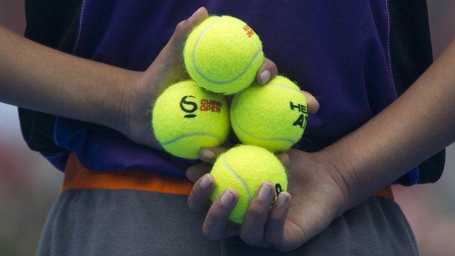 A ball boy holding tennis balls