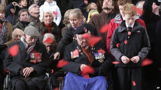 World War II veteran from Liverpool, Alan Rowe, center, watches paper poppies fall during an Armistice Day ceremony under the Menin Gate in Ypres, Belgium