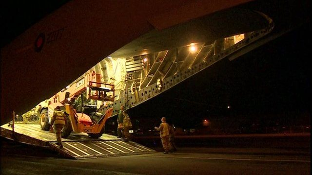 A digger is loaded onto the plane