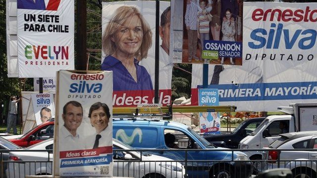 A street corner is filled with election campaign signs, including presidential candidate Evelyn Matthei