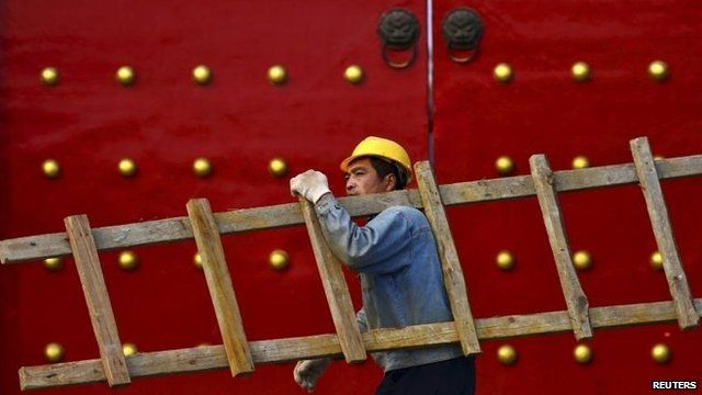 A worker carrying a ladder walks past a palace used by ancient emperors in Shenyang, Liaoning province