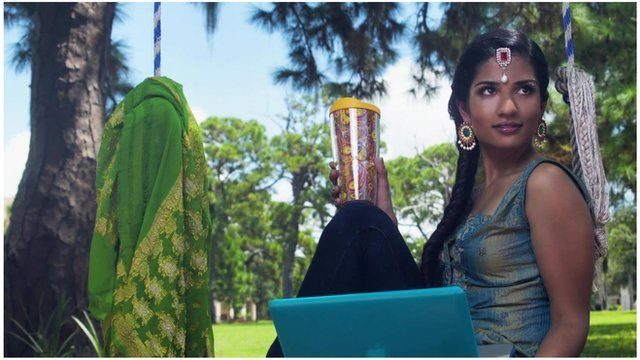 A businesswoman posing for the Saris to Suits calendar