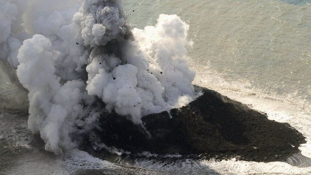Island with smoke and lava spewing out of it