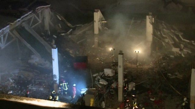 Dust and debris as another section of roof collapses into the building