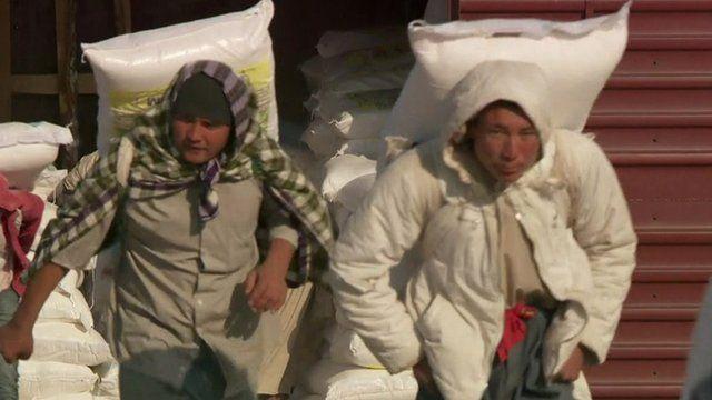 Men unload train of goods