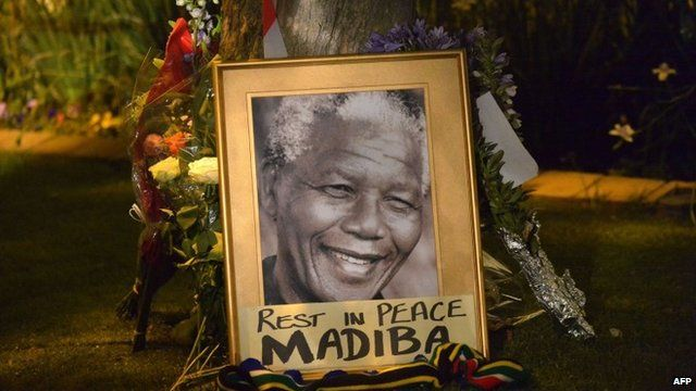 """Flowers and poster reading """"Rest in peace Madiba"""""""