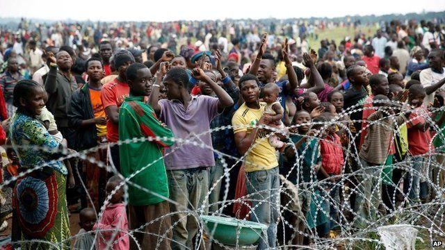 Crowds standing behind razor wire, cheering