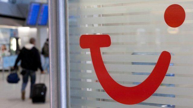 Man walking past Tui logo at airport