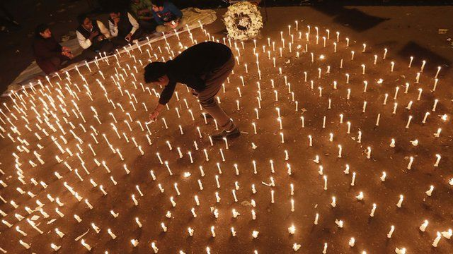 A protester lights a candle at a vigil in New Delhi