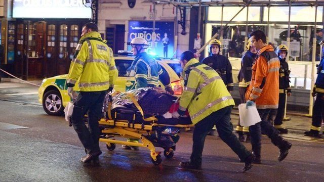 An injured person on a stretcher outside the Apollo Theatre