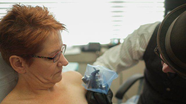 Woman having her nipple tattooed