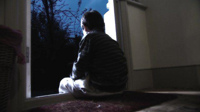 A child sitting in a doorway