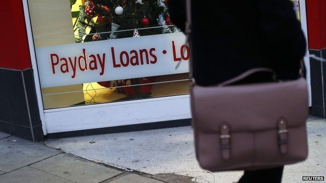Woman walks past payday loan shop