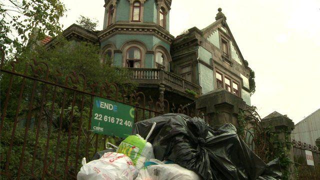 A derelict building with rubbish sacks