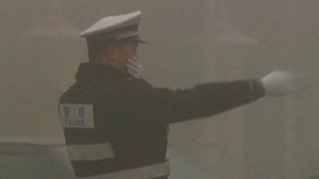 Beijing traffic officer in smog