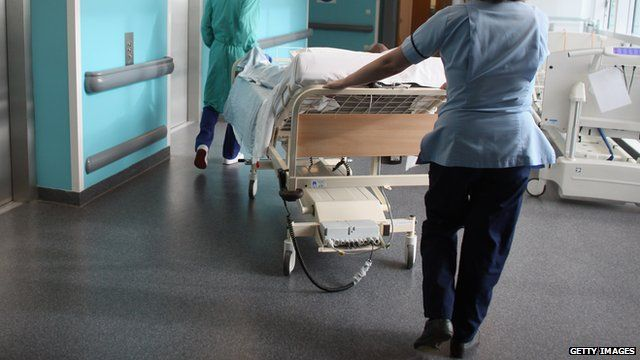 A nurse pushing a hospital bed