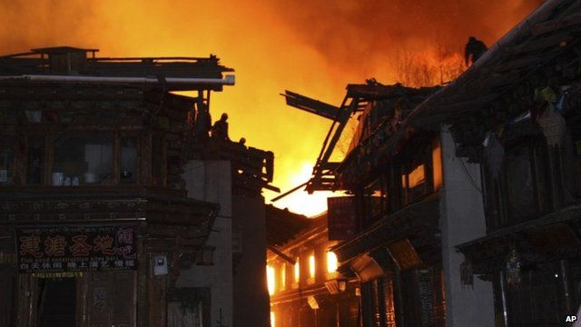 Firefighters work on roofs of buildings while a fire ravages ancient Dukezong town in Shangri-la county, in south-western China's Yunnan province