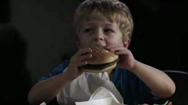 Young boy eats burger
