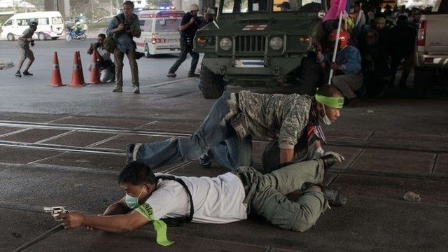 A Thai pro-election protester takes cover and aims his gun before shooting towards Thai anti-government protesters