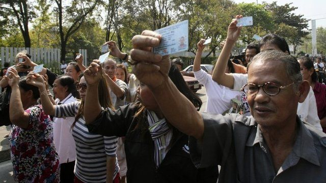 Pro-election supporters hold up their ID cards to demand to vote outside Din Daeng polling station in Bangkok Sunday, Feb. 2, 2014
