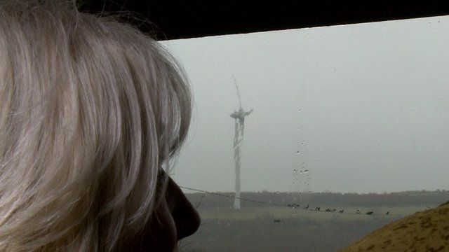 Woman looks out of window at wind turbine