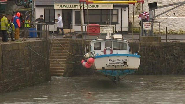 Boats are being removed from the harbour in Porthleven
