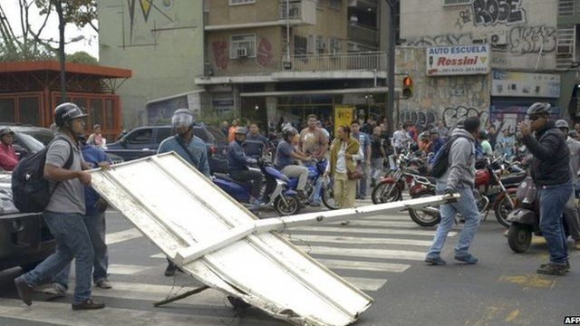 Demonstrators block a street with a traffic sign during a protest against the government of Venezuelan President Nicolas Maduro, in Caracas on 24 February, 2014
