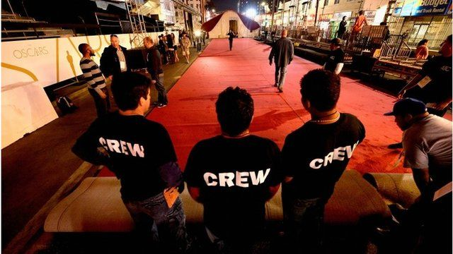 Crew members helping to install the Oscars red carpet