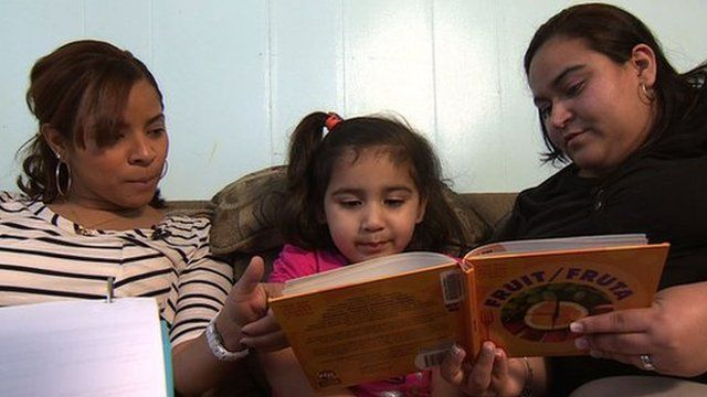 A mother and daughter get help with reading from a counsellor