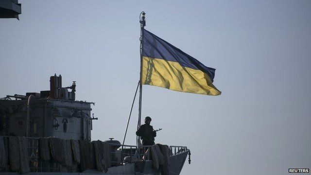 Member of Ukrainian navy on board ship flying Ukrainian flag