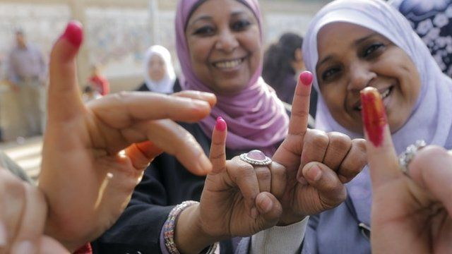 Egyptian women show their inked fingers after casting their votes at a polling station in Cairo