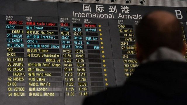 Man stands under arrivals board showing flight information