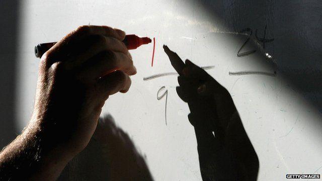 Maths teacher writing fractions on a whiteboard