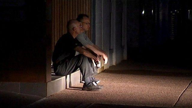 Men sitting outside at night during the Darwin blackout