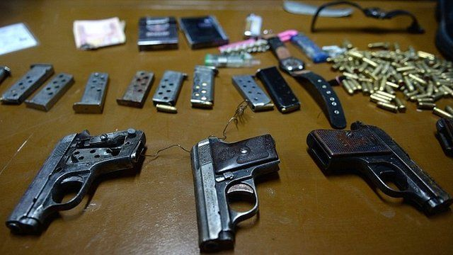 Handguns used by the hotel attackers are displayed to the media during a news conference in Kabul