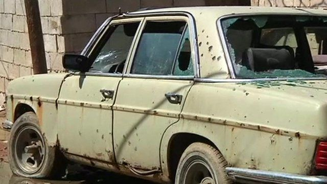 Old car riddled with bulletholes and shattered windows