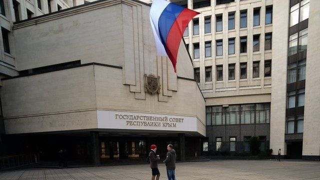 """People stand under a Russian flag in front of the Crimean parliament bearing a new sign reading """"State council of Crimean Republic"""" in central Simferopol"""