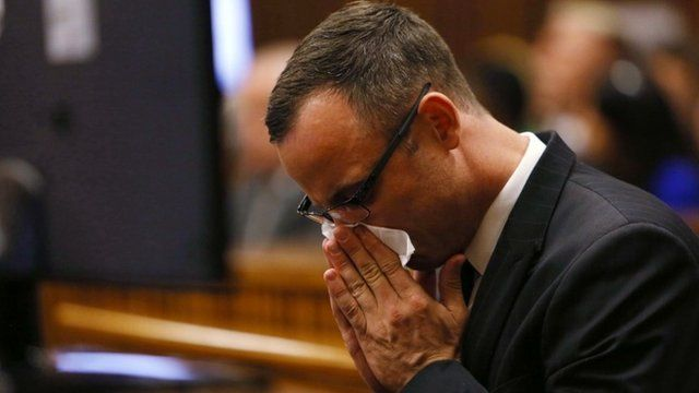 Paralympic track star Oscar Pistorius wipes his nose as he sits in the dock ahead of his trial for the murder of his girlfriend Reeva Steenkamp