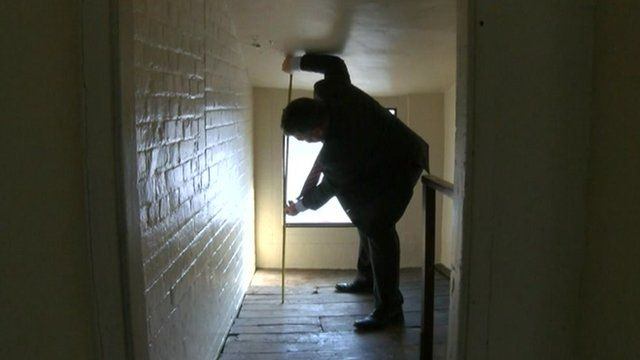 Kevin Burch measuring the inside of a house