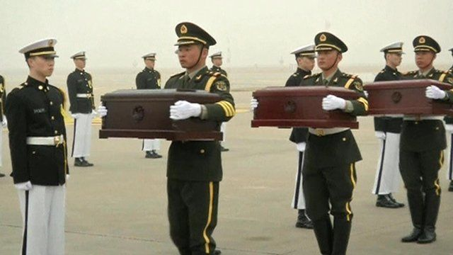 Chinese soldiers holding the coffins
