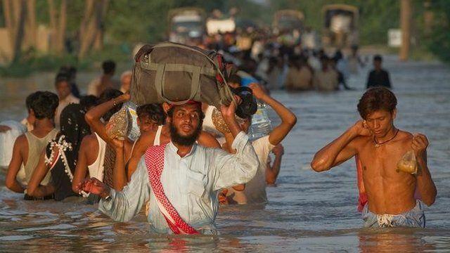 Villagers wade through flood waters in the village of Baseera near Muzaffargarh in Pakistan