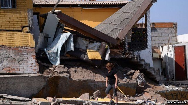 A woman walks next to a destroyed house in Iquique, northern Chile
