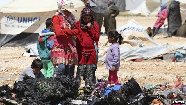 Syrian refugees children look at the remains of their belongings, which were damaged during a clash between security forces and Syrian refugees, at Zaatari refugee camp in the Jordanian city of Mafraq, near the border with Syria, April 6, 2014