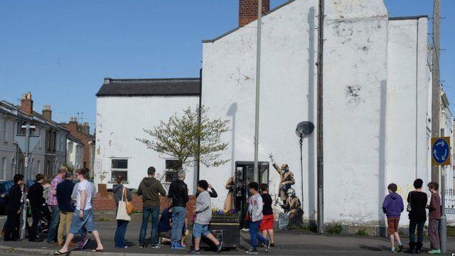 People looking at street art in Cheltenham