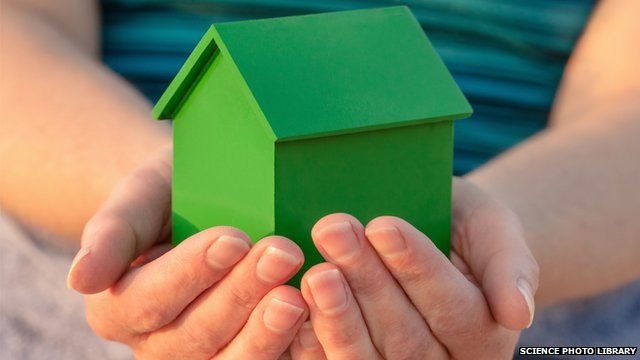 Person holding model house