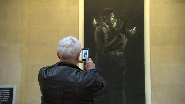 Man takes photo on phone of Banksy art