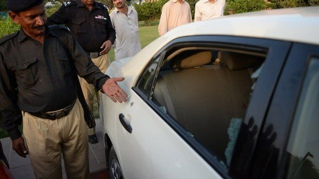 A Pakistani policeman points to a bullet hole