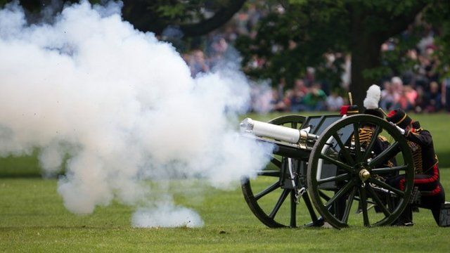 "Members of the public watch as the Kings Troop Royal Horse Artillery, fire a 41 Gun Royal Salute performed in honour of Britains Queen Elizabet""s 88th birthday, in Green Park, London"
