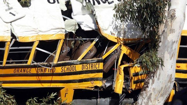 The wreckage of a school bus is seen as it leans against a eucalyptus tree, after it veered off the road in Anaheim, California April 24, 2014