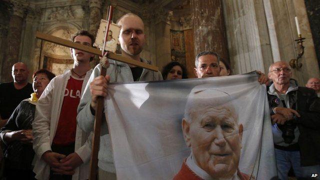 Polish pilgrims hold a flag portraying Pope John Paul II during a vigil prayer